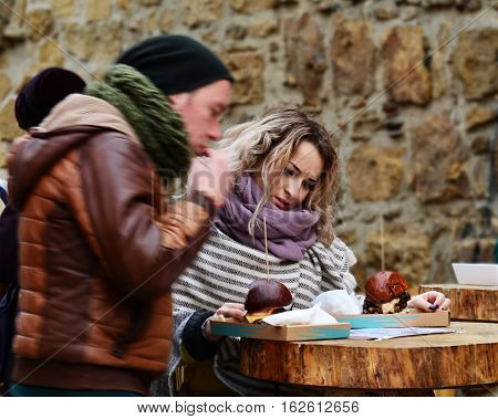 CLUJ-NAPOCA ROMANIA - DECEMBER 17 2016: Beautiful young woman tries to choose one of two burgers at a street food table with an undecided face expression