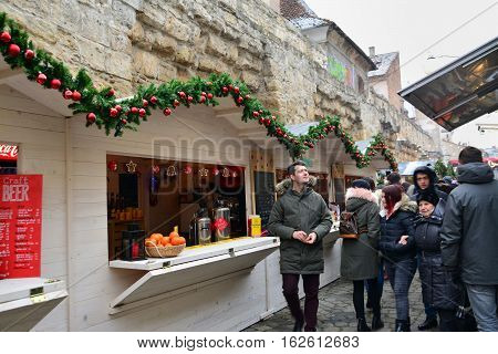 CLUJ-NAPOCA ROMANIA - DECEMBER 17 2016: People buy street food and have a drink at the Street Food Festival winter edition. Vendors in stalls sell tasty fast food from different cultures.