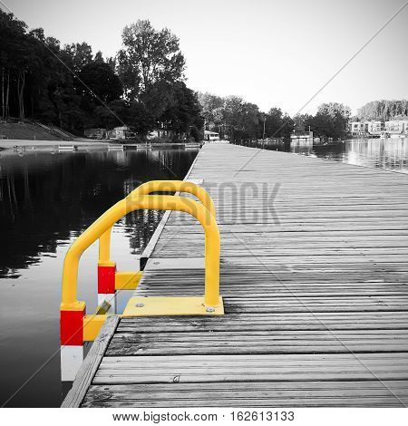 View of a wooden pier with ladder on the pond