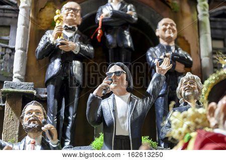 Naples Italy - December 9 2016: San Gregorio Armeno statuettes handmade representatives famous celebrities sports politics music and religion. In the foreground the popular singer Renato Zero.