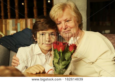 boy with grandma and red roses hugging celebrate granni birthday