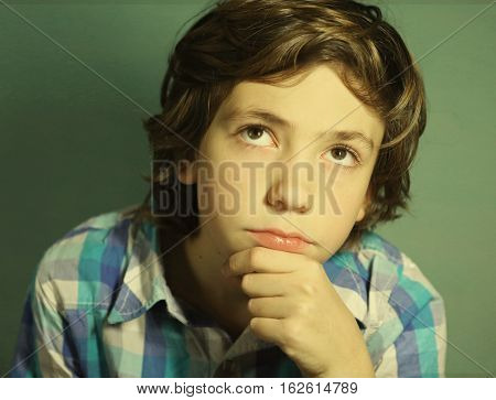 preteen handsome boy think over difficult issue close up portrait
