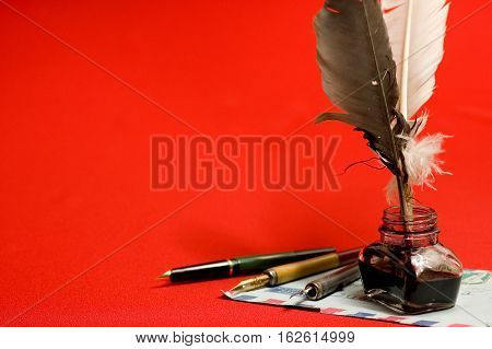 Antique Feather And Inkwell. On A Red Table