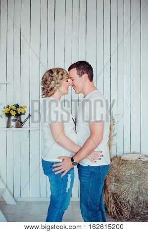 Young Attractive Couple: Pregnant Mother And Happy Father Standing On The White Wooden Background Wi