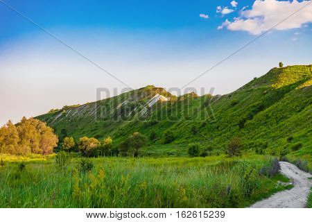 Green chalk hills under blue sky. The multilayered archaeological monument - Krapivinskaya settlement Belgorod region Russia. Summer landscape.