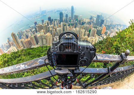 Close up of a professional camera on the tripod while photographing the Victoria Harbour skyline from Lugard Road Lookout at Victoria Peak, the highest mountain in Hong Kong Island. Fisheye lens.