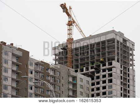 Construction of multi-storey residential concrete home. Wall insulation. Tower crane.