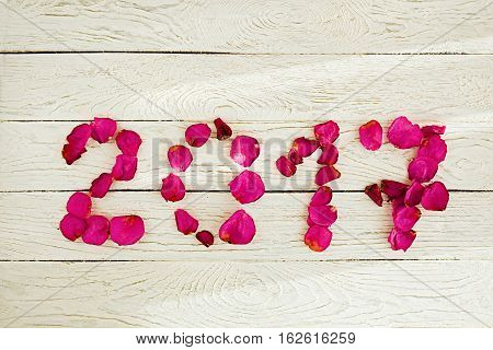 Flat lay of 2017 New Year sign with rose petals on white wooden background