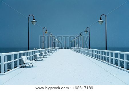 Pier covered with snow. Snowy moody weather. Gdynia, Poland.
