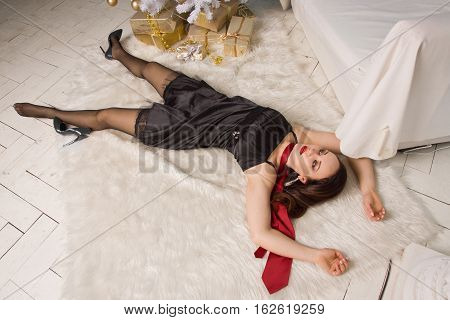 Strangled Beautiful Woman In Black Dress Lies Near The Christmas Tree On The Floor.