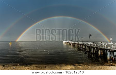 Blue sky and a rainbow over small sandy stream on beach