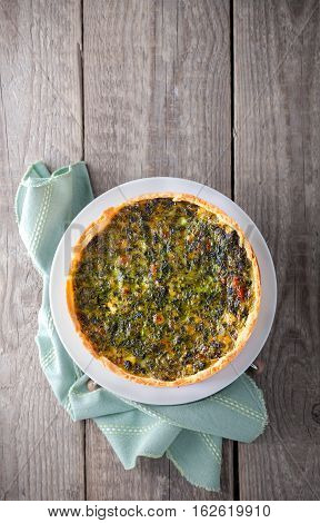 Fresh Spinache quiche on a wooden surface.