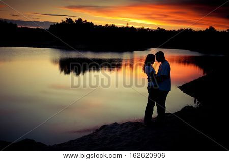 Couple kissing on the beach with a beautiful sunset in background, man lifting the woman
