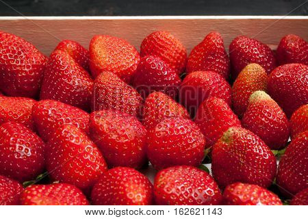 Background from freshly harvested strawberries in wooden box