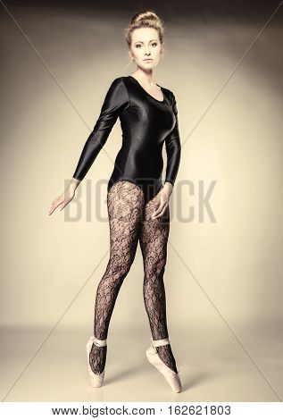 Graceful beautiful woman ballet dancer full length studio shot gray background