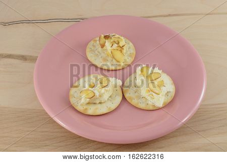 Slices of white chocolate amaretto cheese ball with almonds on table water crackers