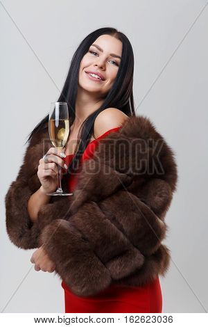 Portrait of brunette in mink coat and red dress with glass of champagne on empty gray background
