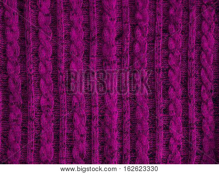 Violet knitted pattern background part of beautiful sweater. Hobbies. Knitted ornament. Copy space