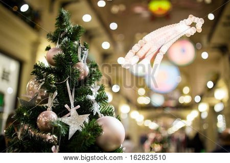 Festive fir tree with purple baubles and stars on a blurred background with lights
