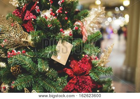 Christmas tree decorated with flowers and gifts in lobby of building, toned photo