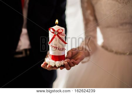 bride and groom holding a beautiful decorative burning candle male and female hand with wedding rings wedding ceremony together forever