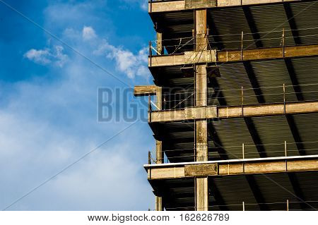 high rise building under construction detail showing steel girders with blue sky and white clouds