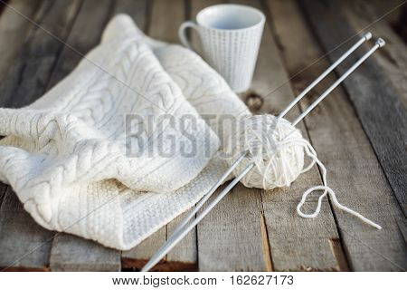 Beautiful white knitted scarf and ball of wool with needles and cup of tea on old wooden table. Cozy winter. Hobbies. Selective focus.