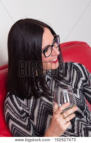 luxurious young women model on red couch drinking wine