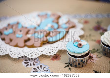 Beautiful blue cupcake and plate with teddy bears cookies biscuits.
