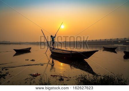 Wooden boat with oarsman at sunset on river Damodar, Durgapur Barrage, West Bengal, India.