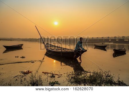 DURGAPUR, INDIA - DECEMBER 20, 2016: An oarsman sits on his boat to shore at sunset on river Damodar near the Durgapur Barrage, West Bengal, India.