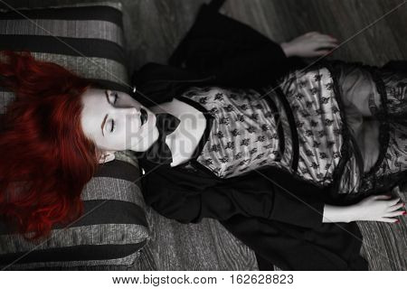 Portrait of red-haired girl in bow tie on a dark background gothic style girl with pigtails a girl in a black dress fashion style sense of style girl in dress and in a black cloak black coat black lips girl lies legs
