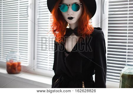 Portrait of red-haired girl in bow tie on a dark background gothic style girl in black clothes style fashion sense of style girl in dress and in a black cloak black coat black lips a girl standing round glasses and a hat in the pot vegetables blinds on th