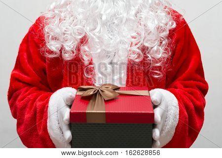 Santa Claus handing a gift box horizontal