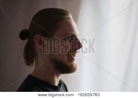 a brutal man in profile with a mustache and a beard with long hair with natural light smiling man