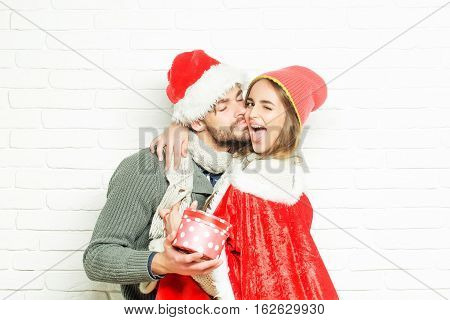 Young happy loving Christmas couple in red santa claus hats of man with gift box and pretty sexy girl or beautiful woman winking on white brick wall