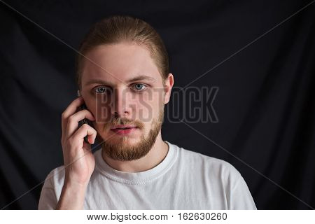 a brutal man in full face with a mustache and beard with slicked hair with natural light on a black background puzzled talking on mobile phone