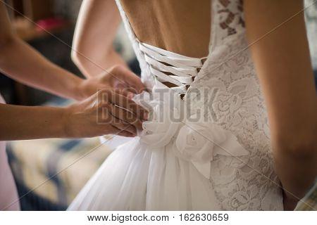 tighten wedding dress on bride, wedding gown