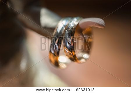 infinity sign of the rings wedding rings on a yellow backgroundwedding bands on the hand of doll