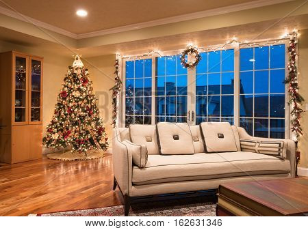 Ornate and decorated Christmas Tree in the corner of living room of modern family home as night falls outside the apartment
