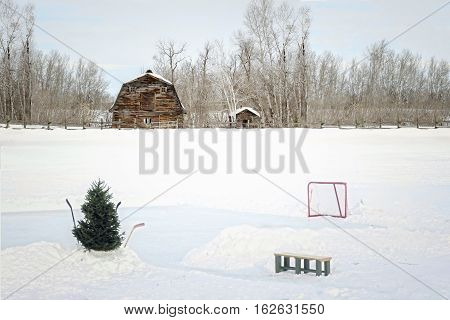 horizontal winter image of a little skating rink with hockey net and sticks stuck in the snow with a bench sitting close by and an old barn in the background.