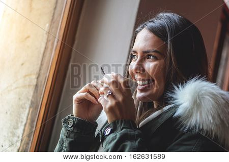 Beautiful young woman having relax drinking a cup of coffee and has foam on her lips - Stunning young girl smiling holding a cup hot beverage and looking out the window