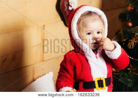 christmas small boy in red santa claus hat and coat touch nose at xmas decorated tree. cute kid at new year holidays celebration on wooden background copy space