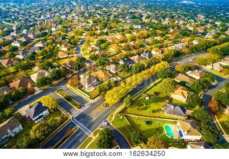 Birds Eye View Suburban Homes outside Austin , Texas near Round Rock , TX New Development with modern architecture and growing number of houses along colorful main street afternoon sunny long shadows poster