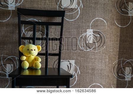 Yellow bear doll sitting on the chair, lonely yellow bear doll, single doll