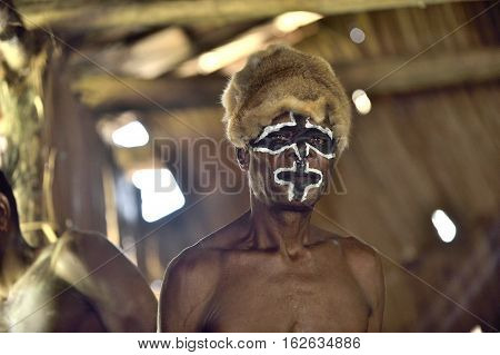 YOUW VILLAGE ATSY DISTRICT ASMAT REGION IRIAN JAYA NEW GUINEA INDONESIA - MAY 23 2016: Portrait of a man from the tribe of Asmat people with ritual face painting on Asmat Welcoming ceremony.