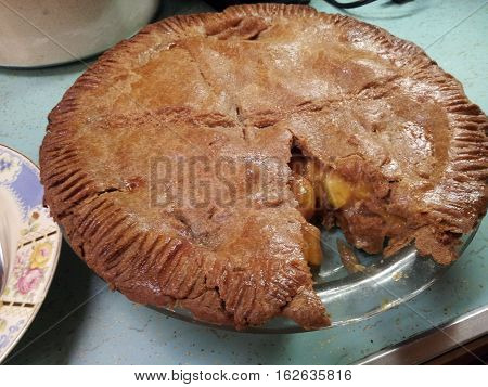 Large homemade apple pie with one piece cut out.