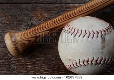A top view image of an old used baseball and wooden baseball bat.