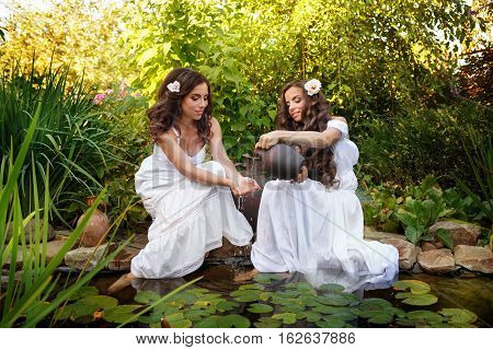 Two sisters in white dresses at the pond with water lilies. Girl pours water from small clay jars in the hands of her sister.