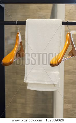 Bathroom Towel - white towel and wood coat hanger on a hanger prepared to use